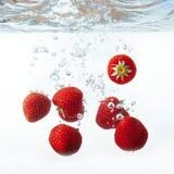 Свежая клубника упала в воду с выплеском на белом backgro Стоковые Изображения RF