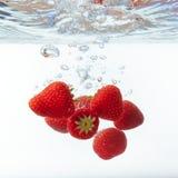 Свежая клубника упала в воду с выплеском на белом backgro Стоковые Фотографии RF