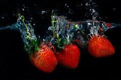 Свежая клубника упала в воду с выплеском на черном backgro Стоковая Фотография RF