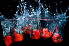 Свежая клубника упала в воду с выплеском на черном backgro Стоковое Изображение