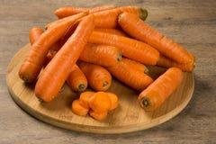 Свежая морковь с листьями зеленого цвета на деревянном столе Стоковые Изображения