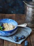 Свежая овсяная каша в голубом шаре с голубиками и старым баком кофе Стоковые Фото