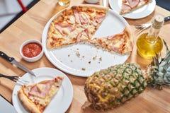 Свежая пицца с ананасом и ветчиной на деревянном столе в ресторане стоковые фото