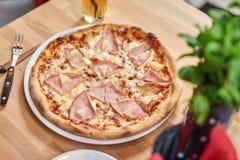 Свежая пицца с ветчиной и ананасом на деревянном столе в ресторане стоковая фотография