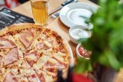 Свежая пицца с ветчиной и ананасом на деревянном столе в ресторане стоковые фотографии rf