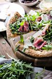 Свежая пицца Rucola с ветчиной Пармы на деревянной cuting доске стоковое изображение
