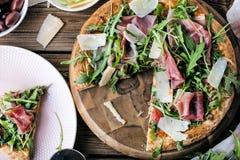 Свежая пицца Rucola с ветчиной Пармы на деревянной cuting доске стоковые фотографии rf