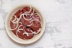 Свежая сырцовая печень с луком в блюде на керамической предпосылке стоковая фотография
