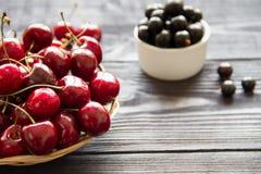 Свежая сладостная вишня в корзине на деревянных предпосылке и blackcur Стоковая Фотография RF