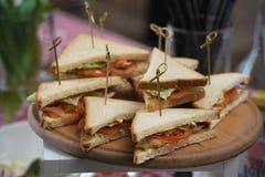 Свежая форма сандвичей клуба триангулярная с томатом на круглой деревянной прерывая доске на таблице в expencive ресторане стоковое изображение rf