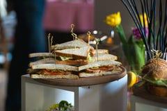 Свежая форма сандвичей клуба триангулярная с томатом на круглой деревянной прерывая доске на таблице в expencive ресторане стоковое фото rf