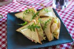 Свежая форма сандвичей клуба триангулярная с томатом на круглой деревянной прерывая доске на таблице в expencive ресторане стоковые фото