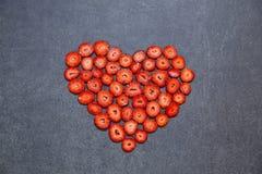 Свежая форма сердца куска клубники на черной предпосылке Стоковое Изображение