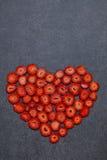 Свежая форма сердца куска клубники на черной предпосылке Стоковая Фотография