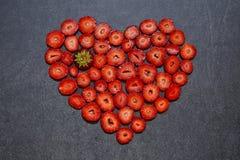 Свежая форма сердца куска клубники на черной предпосылке Стоковые Фото