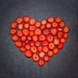 Свежая форма сердца куска клубники на черной предпосылке Стоковые Фотографии RF
