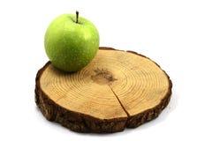 Свежее зеленое запятнанное яблоко и деревянный круг стоковая фотография rf