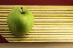 Свежее зеленое запятнанное яблоко на книге стоковые фотографии rf