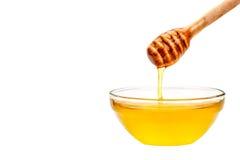 Свежее капание меда от ложки На белой предпосылке Стоковое Изображение RF