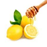 Свежее капание меда от ложки на лимоне На белой предпосылке Стоковое Изображение