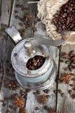 Свежее кофейное зерно в точильщике кофейного зерна на деревянной предпосылке Стоковое Изображение