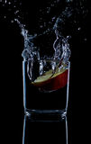 Свежее красное яблоко с капельками воды против черного отражения предпосылки Стоковое фото RF