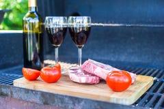 Свежее мясо, овощи и бутылка вина на барбекю outdoors Стоковые Изображения