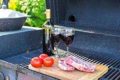Свежее мясо, овощи и бутылка вина на барбекю outdoors Стоковое Фото
