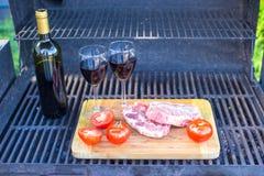 Свежее мясо, овощи и бутылка вина на пикнике outdoors стоковое изображение
