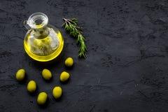 Свежее оливковое масло в стеклянном опарнике около зеленых оливок и ветви розмаринового масла на черном космосе взгляд сверху пре Стоковые Фото