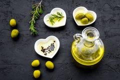 Свежее оливковое масло в стеклянном опарнике около зеленых оливок и ветви розмаринового масла на черном взгляд сверху предпосылки Стоковая Фотография RF