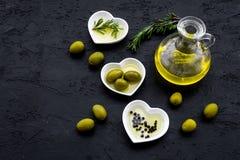 Свежее оливковое масло в стеклянном опарнике около зеленых оливок и ветви розмаринового масла на черном космосе взгляд сверху пре Стоковые Фотографии RF