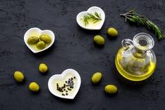 Свежее оливковое масло в стеклянном опарнике около зеленых оливок и ветви розмаринового масла на черном взгляд сверху предпосылки Стоковые Фотографии RF