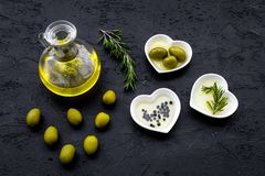 Свежее оливковое масло в стеклянном опарнике около зеленых оливок и ветви розмаринового масла на черном взгляд сверху предпосылки Стоковое фото RF