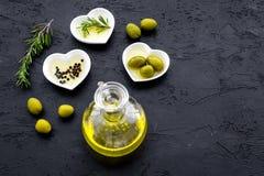 Свежее оливковое масло в стеклянном опарнике около зеленых оливок и ветви розмаринового масла на черном космосе взгляд сверху пре Стоковое Изображение