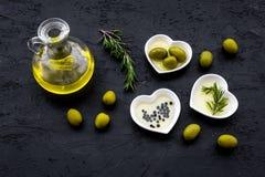Свежее оливковое масло в стеклянном опарнике около зеленых оливок и ветви розмаринового масла на черном космосе взгляд сверху пре Стоковая Фотография RF