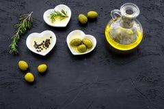 Свежее оливковое масло в стеклянном опарнике около зеленых оливок и ветви розмаринового масла на черном космосе взгляд сверху пре Стоковое Изображение RF