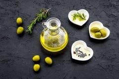 Свежее оливковое масло в стеклянном опарнике около зеленых оливок и ветви розмаринового масла на черном взгляд сверху предпосылки Стоковая Фотография