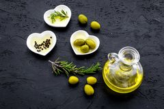 Свежее оливковое масло в стеклянном опарнике около зеленых оливок и ветви розмаринового масла на черном космосе взгляд сверху пре Стоковое фото RF