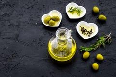 Свежее оливковое масло в стеклянном опарнике около зеленых оливок и ветви розмаринового масла на черном космосе взгляд сверху пре Стоковое Фото