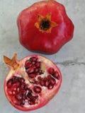 Свежее рубиновое красное гранатовое дерево и отрезанная половина на сером и белом каменном фоне Стоковые Изображения