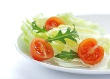 Свежее смешивание салата с томатами вишни и rucola на белой плите Стоковое Изображение
