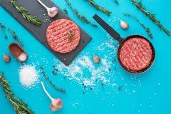Свежее сырцовое мясо говядины с травами и солью на предпосылке бирюзы Стоковые Фото