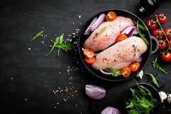 Свежее сырцовое мясо, филе marinated с специями, лук и томаты цыпленка на черной предпосылке Стоковые Фотографии RF