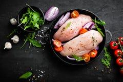 Свежее сырцовое мясо, филе marinated с специями, лук и томаты цыпленка на черной предпосылке Стоковое фото RF
