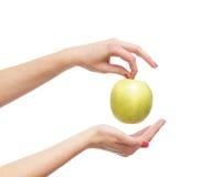 Свежее яблоко, котор держат в красивейших женских руках на белизне Стоковое Изображение RF