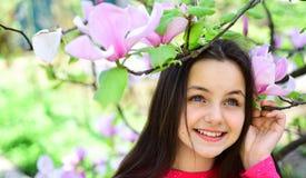 Свежесть весны Милая девушка около цветя дерева наслаждается цветением магнолии Свое время весны Прелестная улыбка девушки в парк стоковые фотографии rf