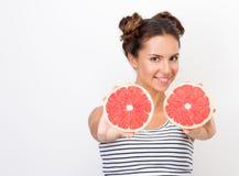 Свежесть и vivacity Молодая жизнерадостная женщина показывая красные половины грейпфрута Стоковое Изображение RF