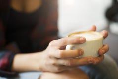 Свеже заваренная чашка кофе, который держат руки девушек Стоковые Изображения