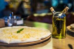Свеже испеченная пицца focaccia с сыр пармесаном на деревянной стойке на деревянном столе Стоковое Фото